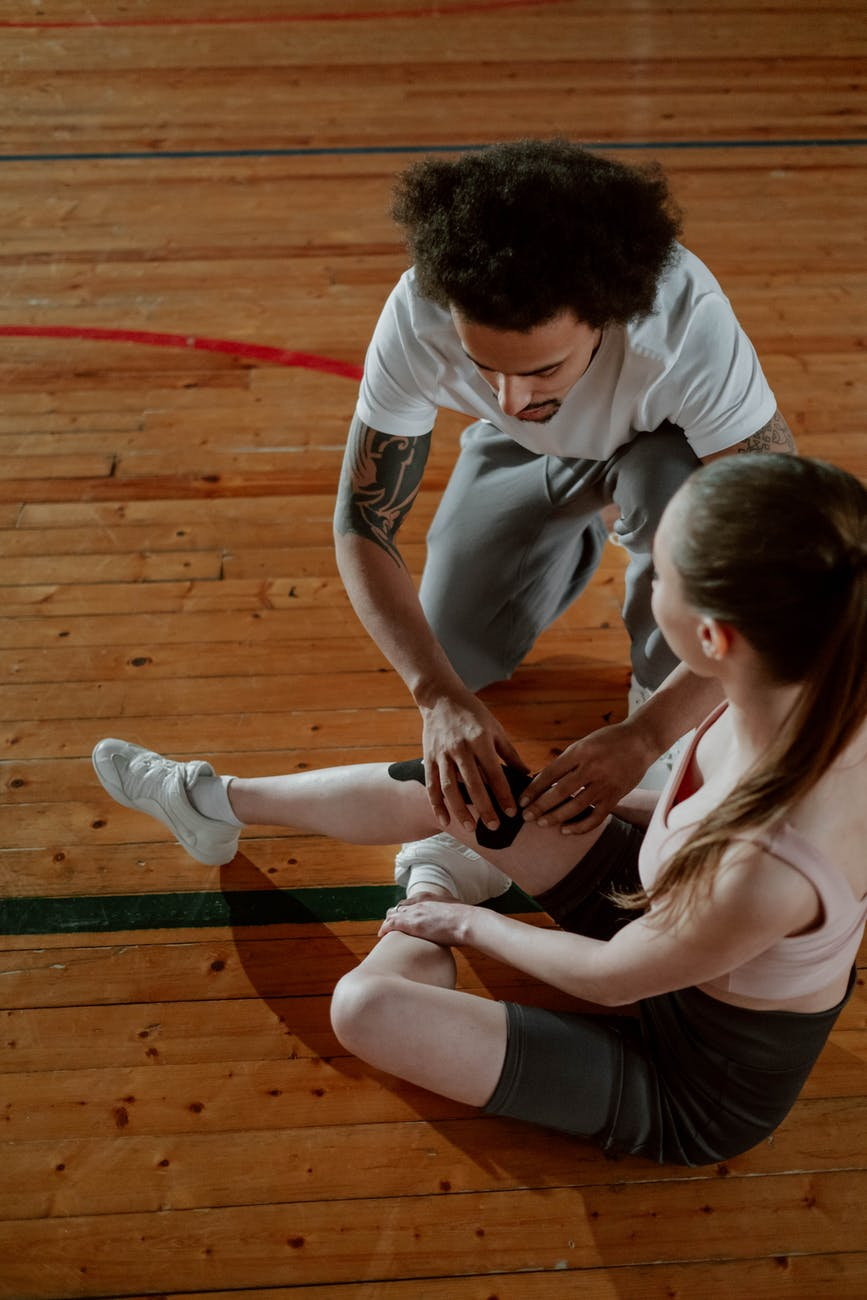 overhead shot of a man putting a kinesio tape on a woman s injured knee